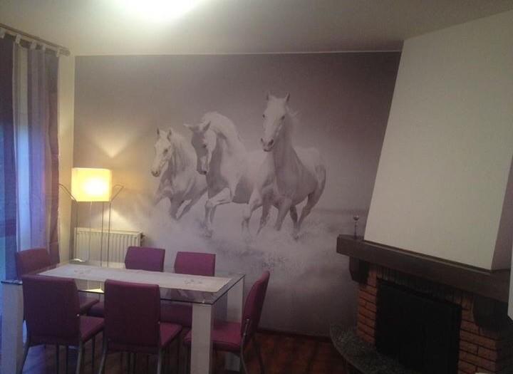 Gigantografia personalizzata su muro con carta da parati stampata.